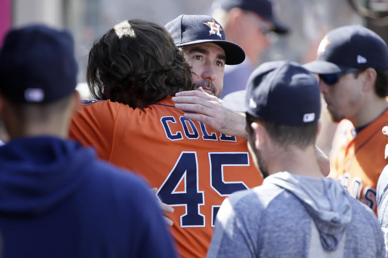 Houston Astros' Justin Verlander, center, hugs starting pitcher Gerrit Cole to congratulate Cole for a possible 20th win of the season, after the fifth inning of a baseball game against the Los Angeles Angels in Anaheim, Calif., Sunday, Sept. 29, 2019. (AP Photo/Alex Gallardo)
