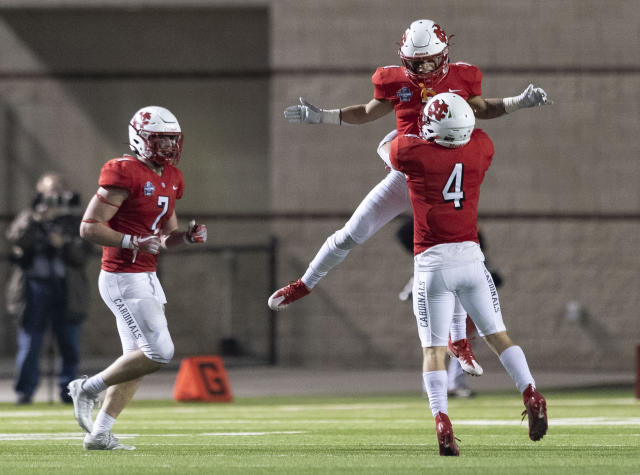 North Central of Illinois defensive back Julian Bell (1) is lifted up into the air by defensive back Dakota Cremeens (4) after intercepting his second Wisconsin-Whitewater pass of the night, during the fourth quarter of the NCAA Division III college football championship game Friday, Dec. 20, 2019, in Shenandoah, Texas. (Jason Fochtman/Houston Chronicle via AP)