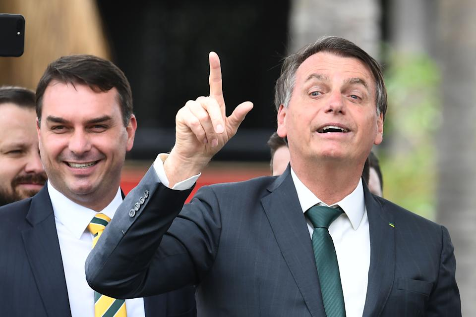 Brazilian President Jair Bolsonaro (R) gestures next to his son, senator Flavio Bolsonaro, during the launch of his new party, the Alliance for Brazil, at a hotel in Brasilia on November 20, 2019. - Bolsonaro left the Social Liberal Party after a disagreement with the party president Luciano Bivar. (Photo by EVARISTO SA / AFP) (Photo by EVARISTO SA/AFP via Getty Images)