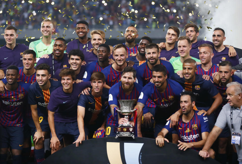 Barcelona players pose with the trophy after winning the Spanish Super Cup soccer match between Sevilla and Barcelona in Tangier, Morocco, Sunday, Aug. 12, 2018. Barcelona won 2-1. (AP Photo/Mosa'ab Elshamy)