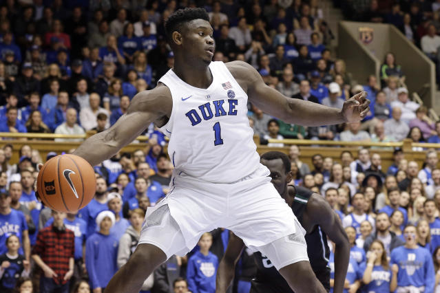 Duke's Zion Williamson (1) saves the ball from going out of bounds while Stetson's Abayomi Iyiola looks on during the first half of an NCAA college basketball game in Durham, N.C., Saturday, Dec. 1, 2018. (AP Photo/Gerry Broome)