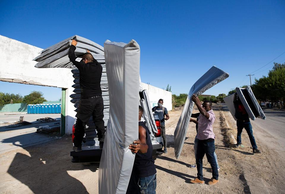 Haitian migrants unload cots at a new designated space for the migrants to stay while they resolve their migratory status in Ciudad Acuña.