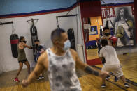 Men wearing face masks to prevent the spread of the coronavirus, exercise at a boxing gym in the southern neighbourhood of Vallecas in Madrid, Spain, Monday, Sept. 28, 2020. (AP Photo/Bernat Armangue)