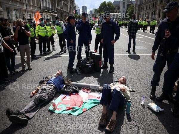 Police officers approach protesters chained to each other during an Extinction Rebellion climate activists' protest [Image Credits: Reuters]