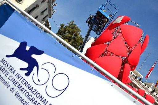 Workers stick the logo of the 69th Venice film festival on a display near the red carpet, August 2012. With much of the traditional cinema sector in a state of flux, Venice film festival participants said the industry is looking to a future in which the Internet will play an ever bigger role