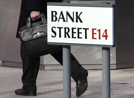 A worker passes a sign for Bank Street in the Canary Wharf financial district in London