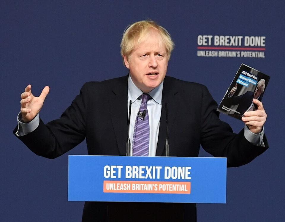 Prime Minister Boris Johnson holds up his party's manifesto during its launch at Telford International Centre in Telford, West Midlands. (Photo: PA Wire/PA Images)
