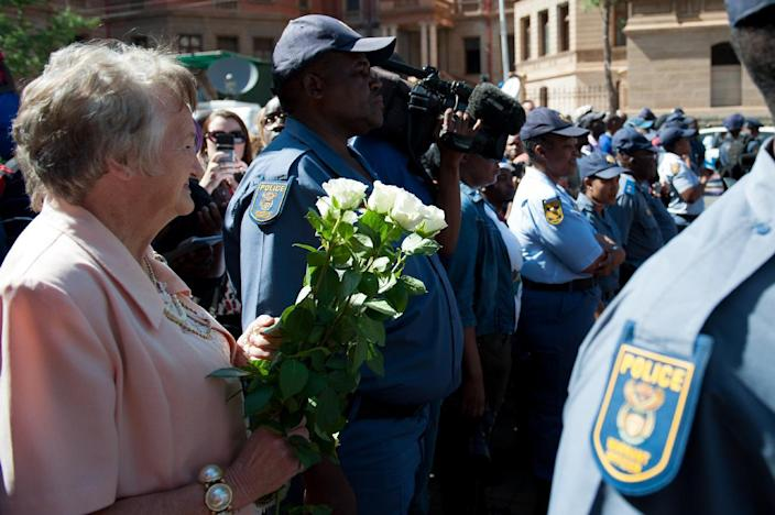 A supporter of South African athlete Oscar Pistorius hold flowers as she waits outside the High Court in Pretoria, on October 21, 2014 (AFP Photo/Stefan Heunis)