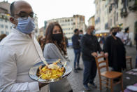 """A man holds a plate of """"Carbonara"""" spaghetti as restaurant owners protest against the government restriction measures to curb the spread of COVID-19, closing restaurants at night, in Rome, Wednesday, Oct. 28, 2020. For at least the next month cafes and restaurants must shut down in early evenings, under a decree signed on Sunday by Italian Premier Giuseppe Conte. (AP Photo/Andrew Medichini)"""