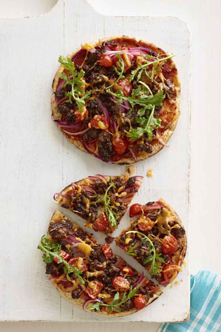 """<p>This easy picnic flatbread combines two all-time family favorites - cheeseburgers and pizza!</p><p><a href=""""https://www.womansday.com/food-recipes/food-drinks/recipes/a13182/cheeseburger-flatbread-pizza-recipe-wdy0115/"""" rel=""""nofollow noopener"""" target=""""_blank"""" data-ylk=""""slk:Get the recipe for Cheeseburger Flatbread Pizza."""" class=""""link rapid-noclick-resp""""><u><em>Get the recipe for Cheeseburger Flatbread Pizza.</em></u></a></p>"""
