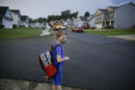 FILE - In this Aug. 3, 2020, file photo, Paul Adamus, 7, waits at the bus stop for the first day of school in Dallas, Ga. As schools reopen around the country, their ability to quickly identify and contain coronavirus outbreaks before they get out of hand is about to be put to the test. (AP Photo/Brynn Anderson, File)