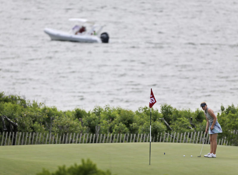 Karinn Dickinson of Norway putts while a boat passes by during a practice round at the U.S. Women's Open golf tournament at Sebonack Golf Club in Southampton, N.Y., Wednesday, June 26, 2013. (AP Photo/Seth Wenig)