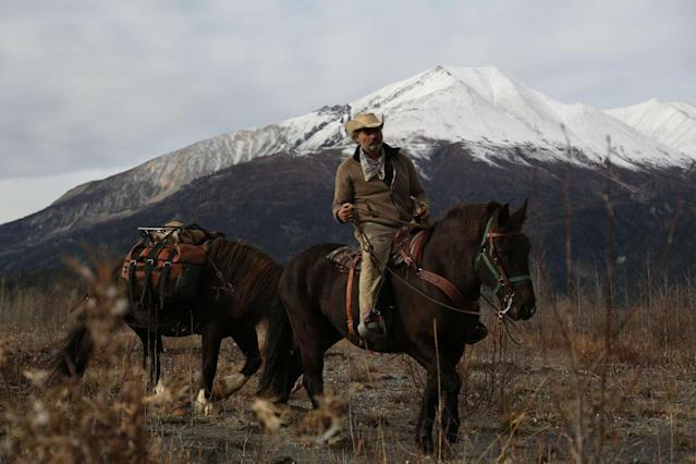 McCarthy, Alaska, USA: Marty Raney riding horse with another horse in tow.