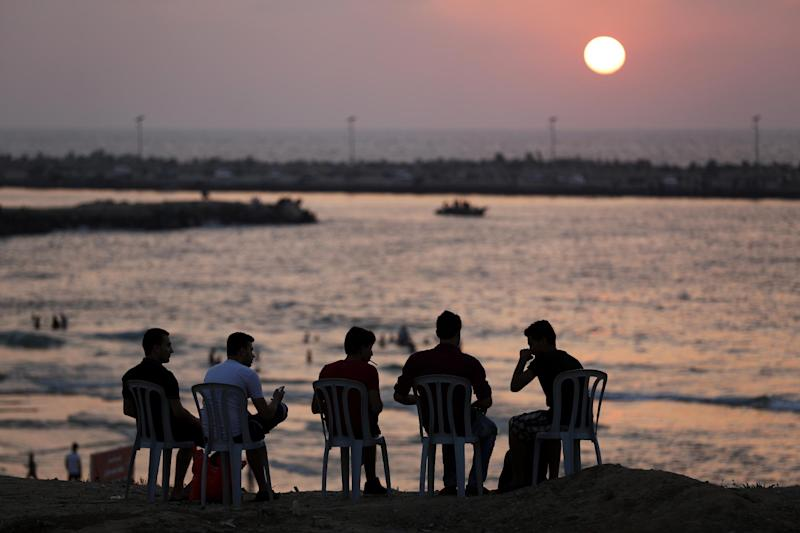 Palestinian youths sit on the beach in Gaza City, during sunset, on August 27, 2014
