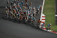The peloton goes into a turn during the men's cycling road race at the 2020 Summer Olympics, Saturday, July 24, 2021, in Oyama, Japan. (AP Photo/Thibault Camus)