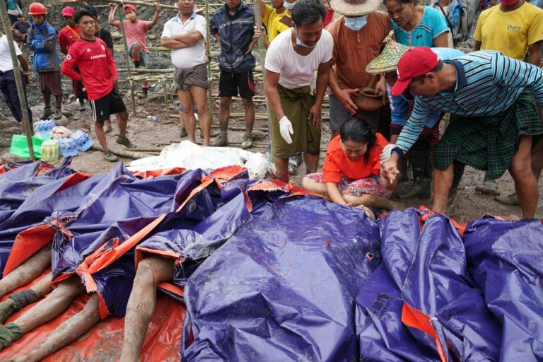 A woman grieves over the bodies in Myanmar on July 2, 2020 (AFP Photo/Zaw Moe Htet)
