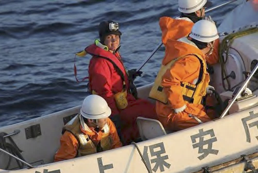 In this photo released by Japan Coast Guard, British adventurer Sarah Outen, facing camera, stands in a boat after she was rescued by Japan Coast Guard in the Pacific Ocean off the northeastern coast of Japan on Friday, June 8, 2012. Outen's blog said she was hit by a storm during her attempted journey around the world, and that her boat rolled over and was damaged. Another Briton on a similar trek was still awaiting rescue. (AP Photo/Japan Coast Guard)