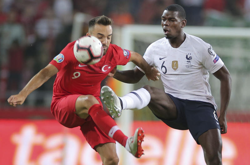 Turkey's forward Kenan Karaman, left, is challenged by France's midfielder Paul Pogba during the Euro 2020 Group H qualifying soccer match between Turkey and France in Konya, Turkey, Saturday June 8, 2019. (AP Photo)