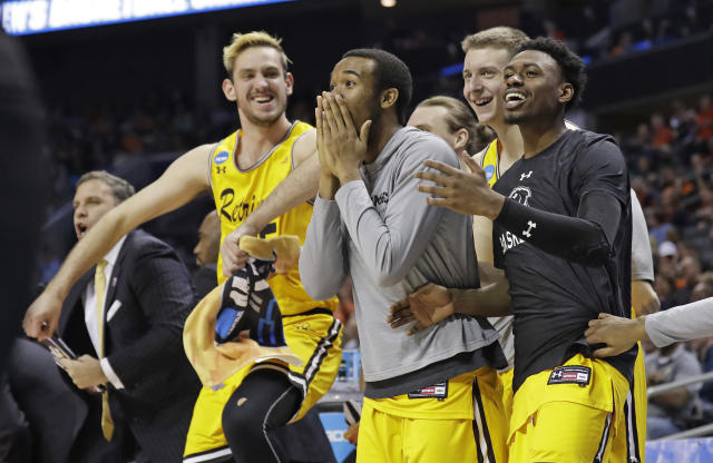 UMBC players celebrate a teammate's basket against Virginia during the second half of a first-round game in the NCAA men's college basketball tournament in Charlotte, N.C., Friday, March 16, 2018. (AP Photo/Gerry Broome)