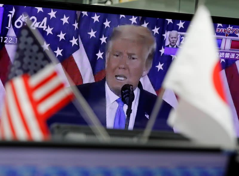 A TV screen showing U.S. President Donald Trump's speech is seen behind Japanese and U.S flags at a dealing room of the foreign exchange trading company Gaitame.com in Tokyo