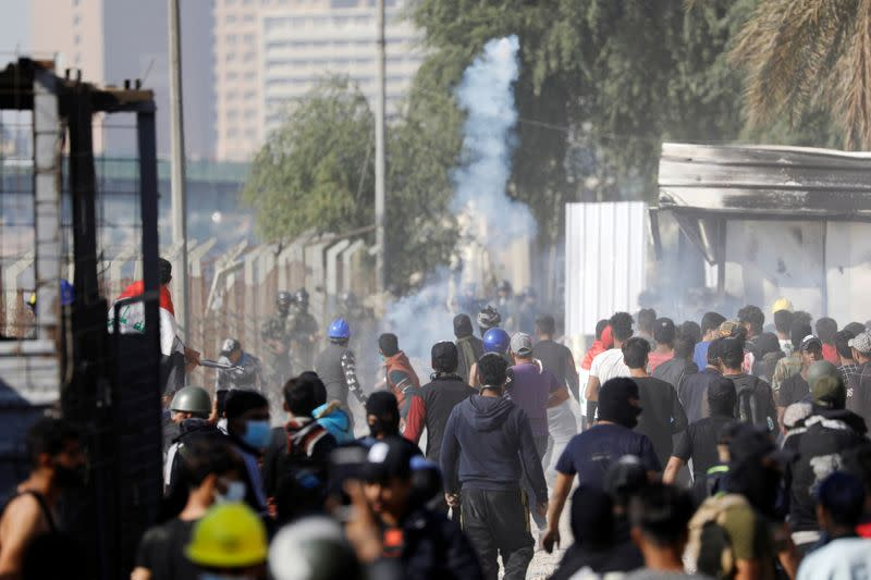 A demonstrator throws tear gas towards Iraqi security forces during the ongoing anti-government protests in Baghdad