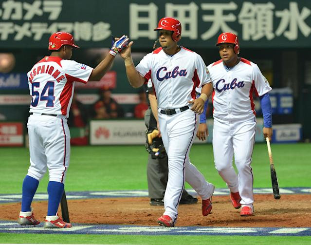 Cuba's Jose Abreu (C) comes into home after hitting a grand slam as his teammate Alfredo Despaigne (L) welcomes him during the fifth inning of their first-round Pool A game in the World Baseball Classic tournament in Fukuoka on March 4, 2013. Cuba beat China 12-0 with a called game at the seventh inning. AFP PHOTO / KAZUHIRO NOGIKAZUHIRO NOGI/AFP/Getty Images