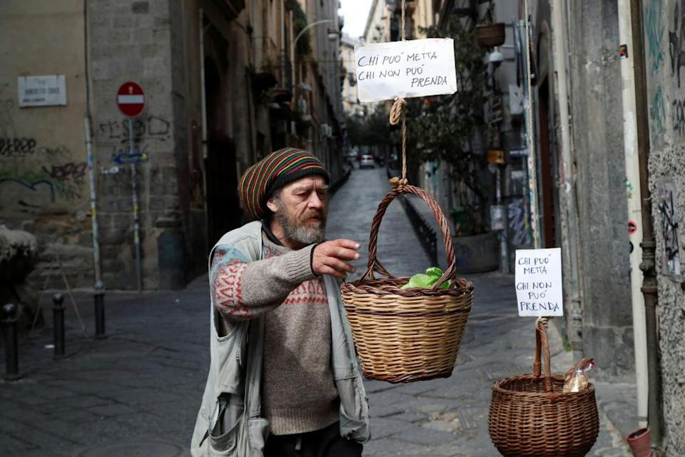 A man reaches for a basket where people can donate or take food in Naples