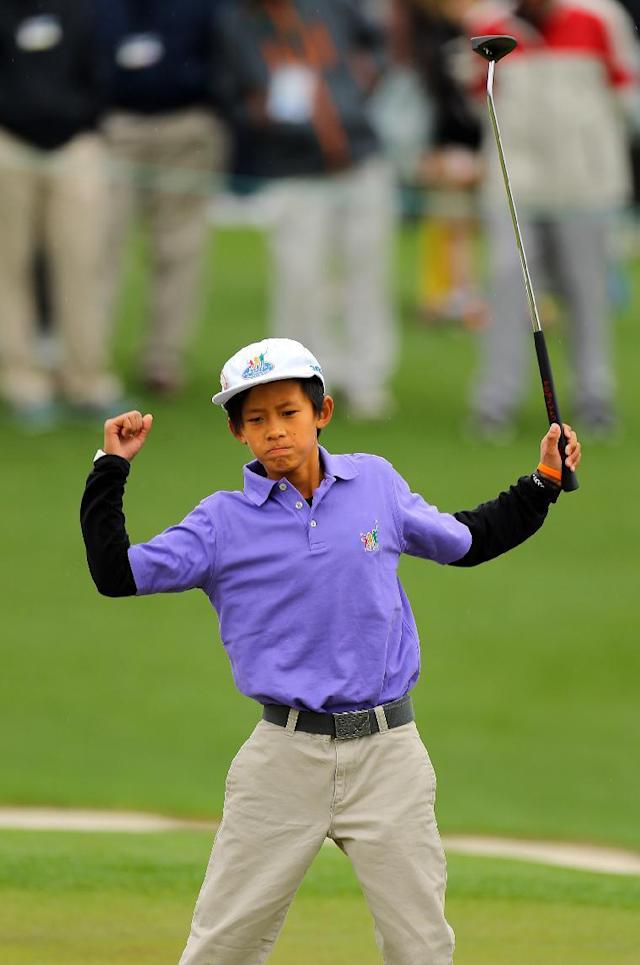Leo Cheng, Northridge, Calif., celebrates after sinking his putt on the 18th green to become the overall champion in the boys 10-11 age group in the first ever Drive, Pitch, and Putt National Finals at Augusta National Golf Club before the Masters on Sunday, April 6, 2014, in Augusta, Ga. (AP Photo/Atlanta Journal-Constitution, Curtis Compton)
