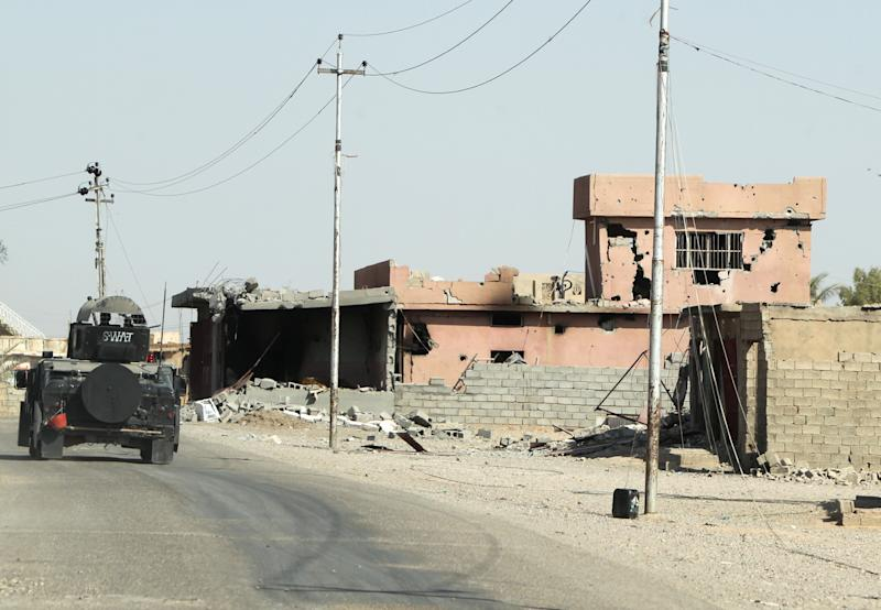 An Iraqi military truck drives past buildings destroyed by fighting with Islamic State group militants, on a road outside of Tikrit on September 3, 2014