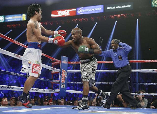 Manny Pacquiao, left, of the Philippines, evades a punch from Timothy Bradley in their WBO welterweight title boxing fight Saturday, April 12, 2014, in Las Vegas. At right is referee Kenny Bayless. (AP Photo/Isaac Brekken)
