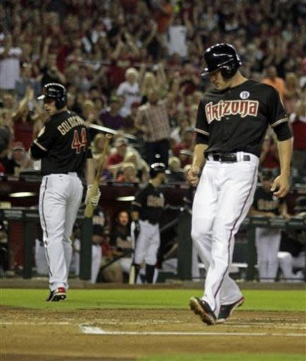 Arizona Diamondbacks A.J. Pollock, right, scores on a wild pitch in the first inning during a baseball game against the Colorado Rockies on Friday, July 5, 2013, in Phoenix. (AP Photo/Rick Scuteri)