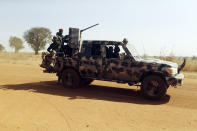 Nigerian soldiers drive past Government Science secondary school in Kankara , Nigeria, Wednesday, Dec. 16, 2020. Rebels from the Boko Haram extremist group claimed responsibility Tuesday for abducting hundreds of boys from a school in Nigeria's northern Katsina State last week in one of the largest such attacks in years, raising fears of a growing wave of violence in the region. (AP Photo/Sunday Alamba)
