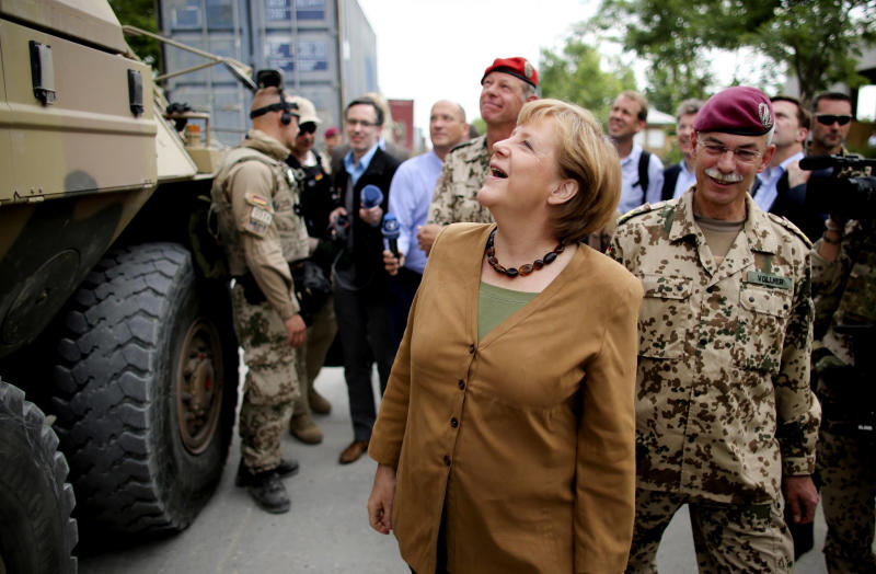 German Chancellor Angela Merkel, center, and German Major General Joerg Vollmer, right, tour the German camp in Kunduz, Afghanistan, Friday, May 10, 2013. Germany's Chancellor Angela Merkel made a surprise to northern Afghanistan to visit her troops less than two weeks after insurgents killed a German special forces soldier and wounded a second, a military spokesman said. Germany is the only NATO nation that is committed to leaving troops in Afghanistan after the coalition completes its scheduled pullout of combat forces next year. The U.S. is likely to deploy several thousand troops if the Afghan government provides them legal protection. (AP Photo/DPA/Kay Nietfeld)