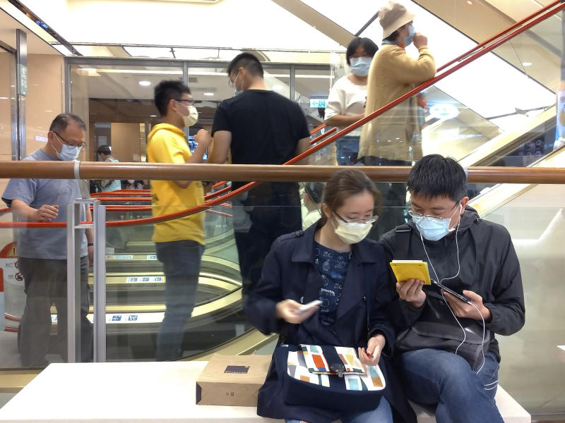 People wear face masks to protect against the spread of the coronavirus at a department store in Taipei, Taiwan, Saturday, March 7, 2020. (AP Photo/Chiang Ying-ying)