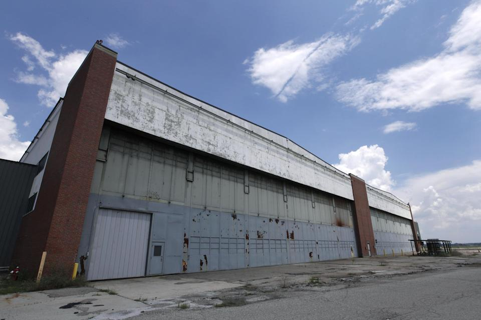 """Part of the former Willow Run Bomber Plant is shown at Willow Run Airport in Ypsilanti Township, Mich., Wednesday, July 17, 2013. The bomber plant west of Detroit was where, at President Franklin Roosevelt's urging, Ford Motor Co. switched from making cars to planes and produced one an hour _ nearly 9,000 B-24 Liberator bombers in all _ to help win the war in Europe. At the time of its 1940s construction, the plant was the largest factory in the world, employing 40,000 men and women, including Rose Will Monroe, who was believed to have been the inspiration for the famed Rosie the Riveter character. The factory went back to auto production for half a century under the General Motors name and closed for good last decade. The plan is to knock it down. But a group of donors are hoping to save at least a piece of it so they can erect a museum dedicated to Detroit's role as the """"Arsenal of Democracy."""" To make that happen, though, organizers need to raise $5 million by Aug. 1. (AP Photo/Paul Sancya)"""