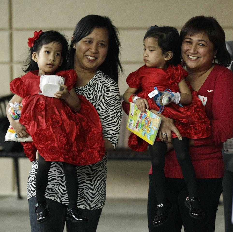 Angelina Sabuco, at left, is held by her mother Ginady Sabuco and twin sister Angelica, is held by aunt Marita Sabuco, at Lucile Packard Children's Hospital, Monday, Nov. 14, 2011 in Stanford, Calif. The twin sisters, who were born joined in the chest an abdomen, are preparing to go home after an intricate surgery by a group of Lucile Packard doctors to separate them. (AP Photo/Marcio Jose Sanchez)