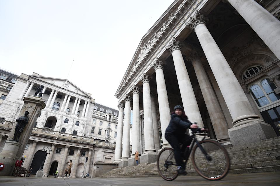A woman cycles past the Bank of England and the Royal Exchange in the City of London.