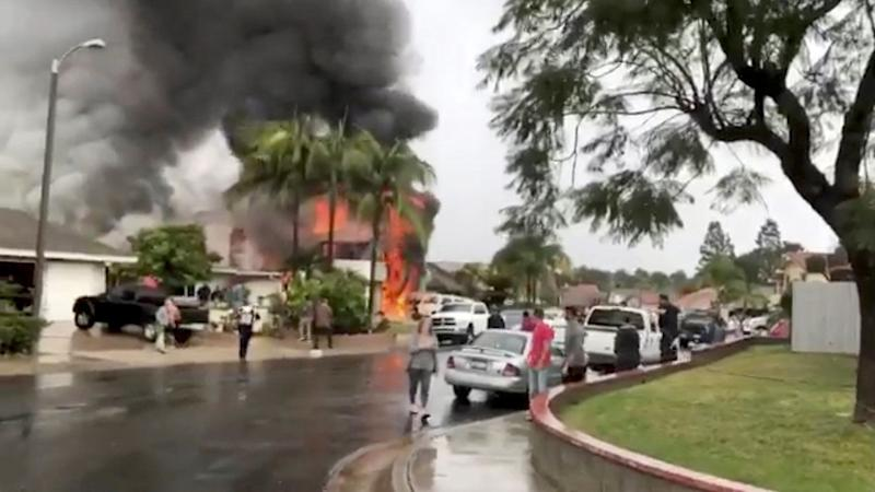 People look as smoke billows after a plane crashed into a house in a residential neighborhood in Yorba Linda, Calif., Feb. 3, 2019, in this still image from video obtained from social media. (Photo: Joshua Nelson/via Reuters)