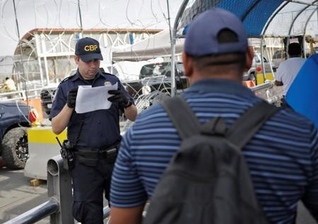 A U.S. Customs and Border Protection officer inspects documents from a Honduran migrant seeking asylum at Paso del Norte International border bridge, in this picture taken from Ciudad Juarez