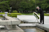 International Olympic Committee President Thomas Bach offers flowers to Hiroshima Memorial Cenotaph during his visit Friday, July 16, 2021, in Hiroshima, western Japan. (AP Photo/Eugene Hoshiko, Pool)