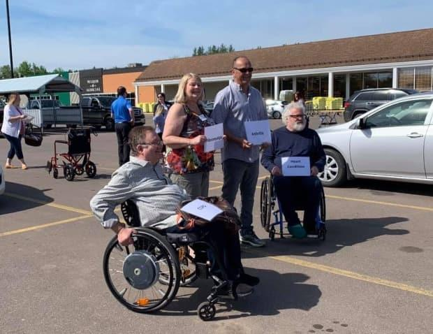 Members of the P.E.I. Council of People with Disabilities held signs indicating the various health conditions that might require a person to need a designated parking permit. (P.E.I. Council of People with Disabilities/Facebook - image credit)