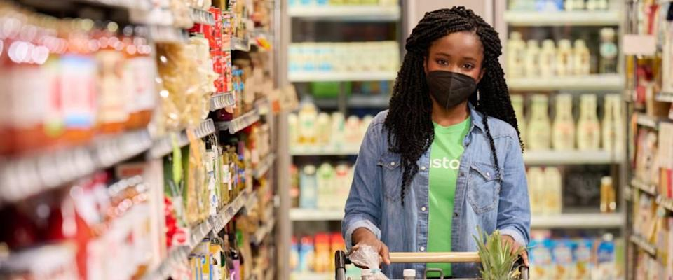 Woman shopping in an Instacart t-shirt in a grocery store, wearing mask.