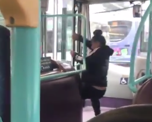 A woman in Manchester pries open a door on a moving bus in order to chase her fleeing boyfriend. (Photo: Sian Bayliss via Twitter)