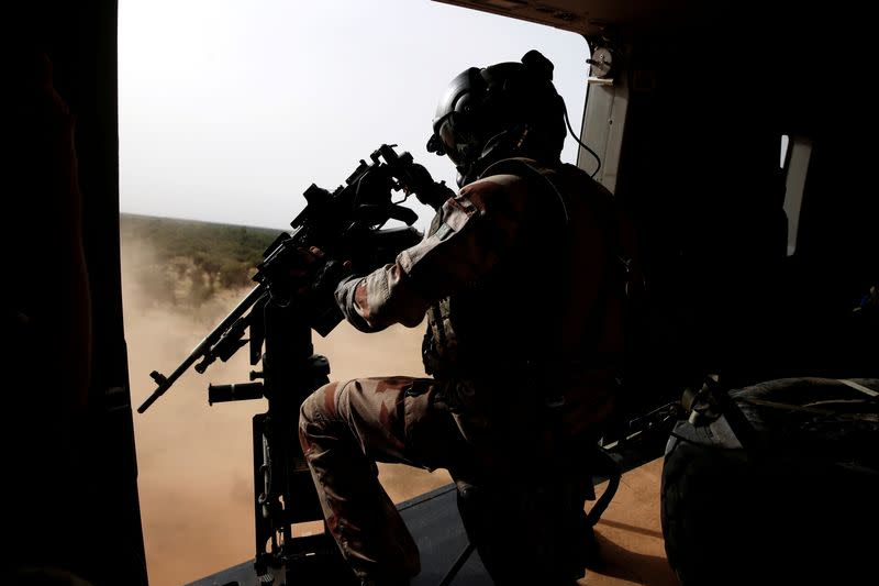 FILE PHOTO: A French soldier mans a machine gun in the door of a NH 90 Caiman military helicopter during Operation Barkhane over Ndaki