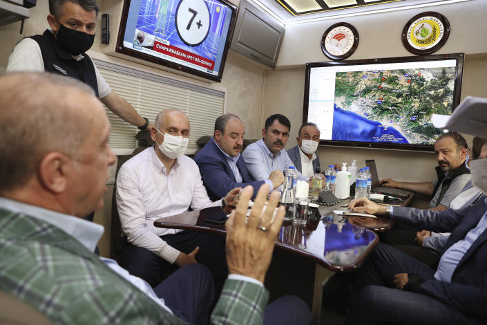 Turkey's President Recep Tayyip Erdogan, front, speaks to his ministers about the wildfires in Manavgat, Antalya, Turkey, Saturday, July 31, 2021. The death toll from wildfires raging in Turkey's Mediterranean towns rose to six Saturday after two forest workers were killed, the country's health minister said. Fires across Turkey since Wednesday burned down forests, encroaching on villages and tourist destinations and forcing people to evacuate.(Turkish Presidency via AP, Pool)