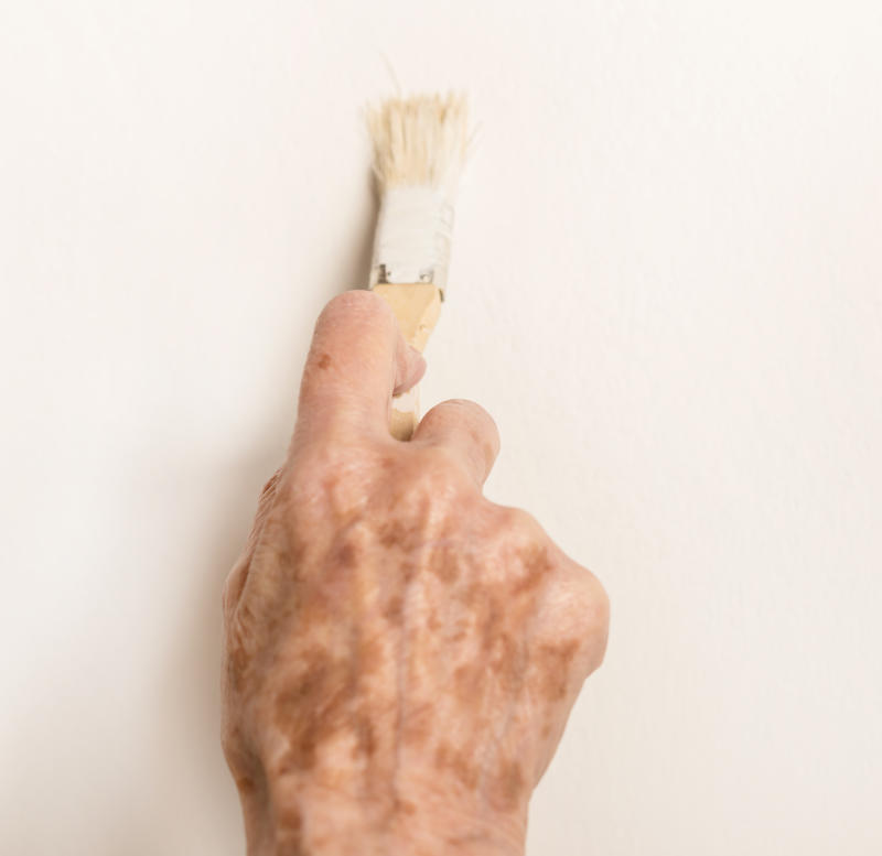 Hand of an old lady holding a small paint brush on the white wall.