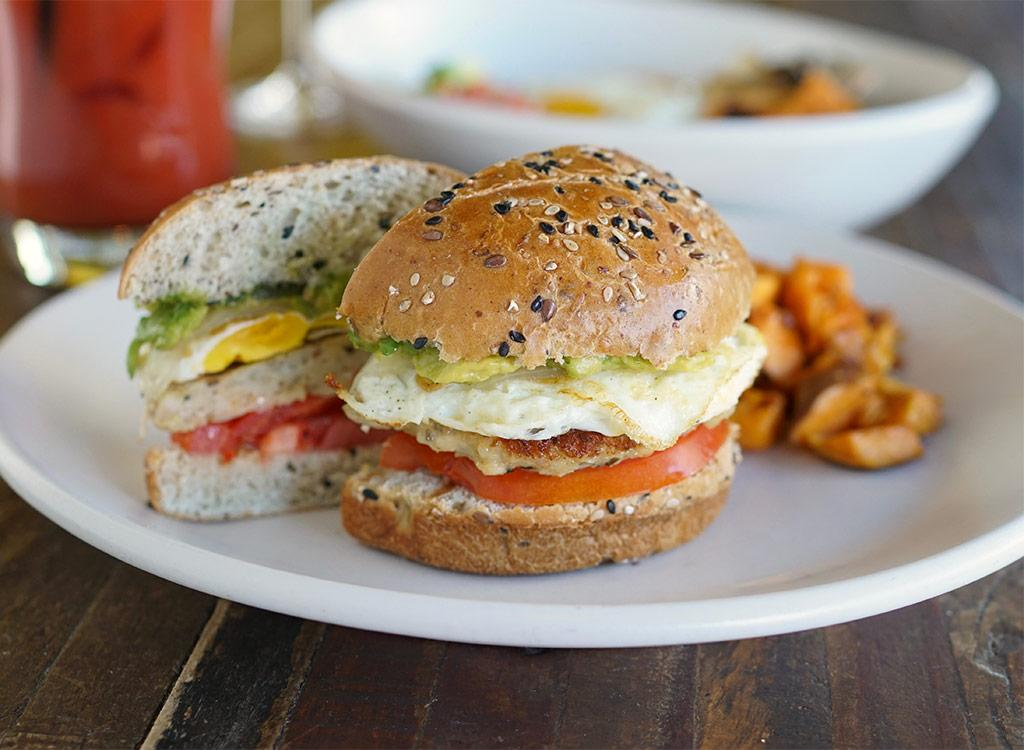 <div>660 calories, 31 g fat (10 g saturated fat), 1,310 mg sodium, 57 g carbs (5 g fiber, 13 g sugar), 37 g protein</div>         Layers of crispy egg, chicken sausage, manchego, tomato, and smashed avocado are nestled into a seeded bun and served with your choice of sweet potato hash or kale salad. Pick this high-protein 'wich to stave off those pesky 2 p.m. munchies.