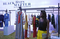Fashion designer Fallylah Nyny Ryke Goungou, from Togo, poses in front her creations, part of the Black Lives Matter Spring Summer 2022 collective fashion event, unveiled during the Milan Fashion Week, in Milan, Italy, Tuesday, Sept. 21, 2021. (AP Photo/Antonio Calanni)