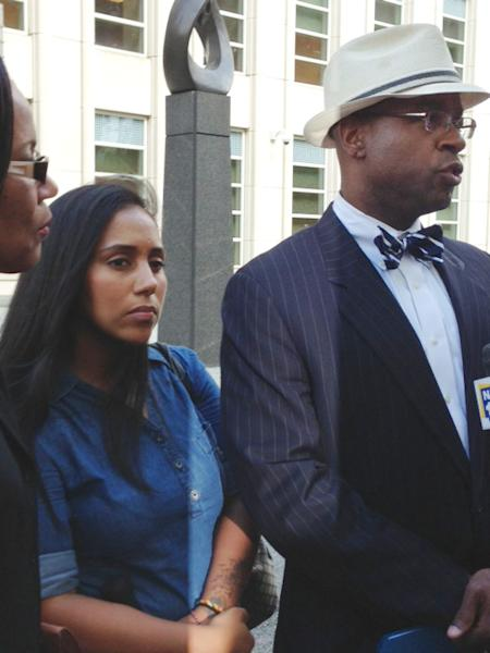 Former Metropolitan Detention Center guard, Nancy Gonzalez, center, listens as her attorney, Anthony Rico, speaks to members of the media outside the federal courthouse in the Brooklyn borough of New York, Wednesday, July 3, 2013. Gonzalez had earlier pleaded guilty to an illegal sex act with inmate Ronell Wilson while he was incarcerated at the facility where she worked. Wilson was convicted in 2006 for the slaying of two police officers. (AP Photo/Tom Hays)