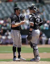 Chicago White Sox pitcher Dylan Covey, left, speaks with catcher Zack Collins in the first inning of a baseball game against the Oakland Athletics, Saturday, July 13, 2019, in Oakland, Calif. (AP Photo/Ben Margot)
